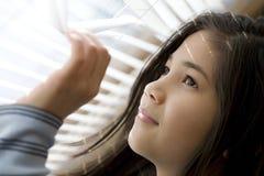 El mirar a escondidas a través de las persianas Fotografía de archivo libre de regalías