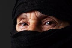 El mirar fijamente musulmán mayor de los ojos de la mujer Fotos de archivo libres de regalías