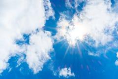 El mirar para arriba el rayo del sol detrás de la nube con la llamarada ligera y el cielo azul Fotografía de archivo