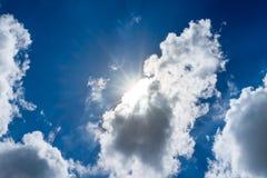 El mirar para arriba el rayo del sol detrás de la nube con la llamarada ligera y el cielo azul Fotografía de archivo libre de regalías