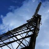 El mirar para arriba un cielo nublado con un molino de viento fotos de archivo