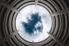El mirar para arriba un cielo tempestuoso a través de un portal Imagen de archivo libre de regalías