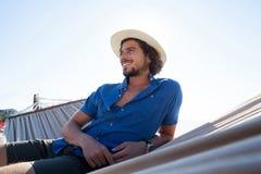 El mirar sonriente ausente mientras que se relaja en la hamaca la playa Foto de archivo libre de regalías