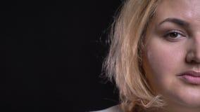 El mitad-retrato del primer de la mujer gorda de mediana edad mira en cámara tranquilamente en fondo negro almacen de metraje de vídeo