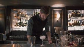 El mixologist hermoso del camarero que pone los cubos de hiela en coctelera con hacer juegos malabares y que va a hacer el cóctel almacen de metraje de vídeo