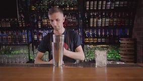 El mixologist hermoso del camarero que pone muchos cubos de hiela en vidrio e ir a hacer el cóctel en barra moderna hermosa almacen de metraje de vídeo