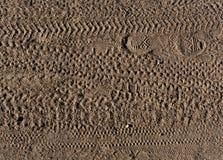 El modelo abstracto de las impresiones del pie y la bici ponen un neumático pistas en la arena Imagen de archivo libre de regalías