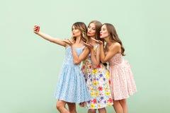 El modelo adulto de los jóvenes de la felicidad tres, selfie macking y envía beso del aire en teléfono elegante de la pantalla en Imagen de archivo