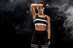 El modelo afroamericano hermoso deportivo, mujer en sportwear hace aptitud que ejercita en el fondo negro para permanecer apto imagenes de archivo