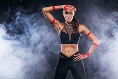 El modelo afroamericano hermoso deportivo, mujer en sportwear hace aptitud que ejercita en el fondo negro para permanecer apto Imagen de archivo libre de regalías