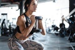El modelo atlético de la aptitud de la mujer joven que hace posiciones en cuclillas ejercita, forma de vida sana del deporte del  fotografía de archivo libre de regalías