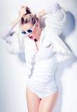 El modelo atractivo de la mujer de la moda se vistió en la presentación blanca de las gafas de sol que llevaba atractiva Foto de archivo libre de regalías