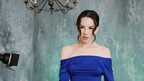 El modelo atractivo elegante de la chica joven se coloca en un vestido azul largo almacen de metraje de vídeo