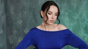 El modelo atractivo elegante de la chica joven se coloca en un vestido azul largo almacen de video
