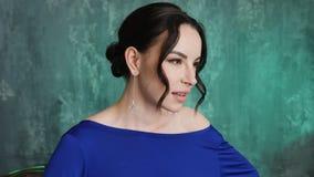 El modelo atractivo elegante de la chica joven se coloca en un vestido azul largo metrajes