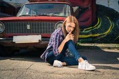 El modelo atractivo joven se está sentando cerca del coche retro Fotografía de archivo libre de regalías