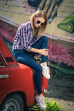 El modelo atractivo joven se está sentando cerca del coche retro Foto de archivo