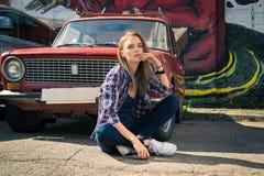 El modelo atractivo joven se está sentando cerca del coche retro Imagen de archivo libre de regalías