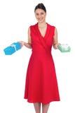 El modelo atractivo sonriente en la tenencia roja del vestido presenta fotografía de archivo libre de regalías
