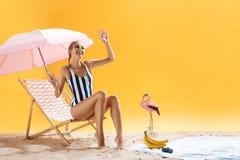 El modelo bonito en ropa de la playa plantea la mano y la sonrisa que agitan Fotografía de archivo libre de regalías