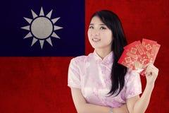 El modelo chino con el vestido del cheongsam sostiene el sobre Fotos de archivo libres de regalías