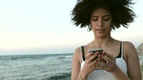 El modelo con el peinado afro oye música en la playa almacen de video