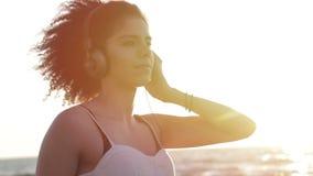 El modelo con un peinado afro muy rizado oye música en la playa almacen de metraje de vídeo