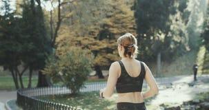 El modelo de la aptitud del deporte en ropa corriente deportiva con las manos blancas del oído de los auriculares de los airpods  almacen de video