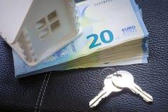 El modelo de la casa, un paquete de dinero digno de 20 euros y las llaves al casero futuro mienten en una placa blanca Imagen de archivo libre de regalías