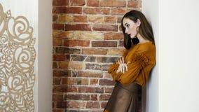El modelo de la muchacha en zapatos de tacón alto y ropa de moda coloca la pared de ladrillo cercana que presenta para la cámara almacen de video
