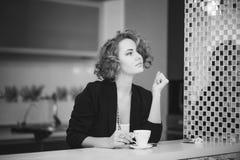 El modelo de la muchacha mira una tabla con la taza de café Imágenes de archivo libres de regalías