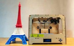 El modelo de la torre Eiffel con la raya azul blanca roja imprimió por la impresora 3D con la impresora 3D en la tabla de madera Fotos de archivo