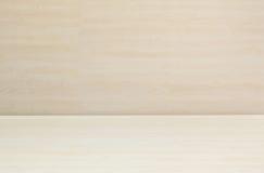 El modelo de madera superficial del primer en el escritorio de madera con la pared de madera borrosa texturizó el fondo bajo luz  Fotografía de archivo libre de regalías