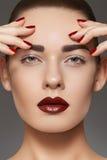 El modelo de manera con los labios construye, manicure en clavos Imagen de archivo