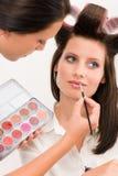 El modelo de manera de la mujer del artista de maquillaje aplica el lápiz labial Imágenes de archivo libres de regalías
