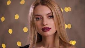 El modelo de moda elegante con el pelo hermoso da vuelta a la cara y mira la cámara, cámara lenta metrajes