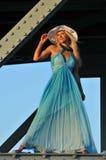 El modelo de moda en el sombrero blanco y el centro turístico azul visten la presentación debajo del puente Imagen de archivo libre de regalías