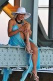 El modelo de moda en el sombrero blanco y el centro turístico azul visten la presentación debajo del puente Foto de archivo libre de regalías