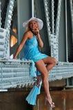 El modelo de moda en el sombrero blanco y el centro turístico azul visten la presentación debajo del puente Fotos de archivo