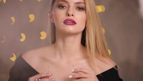 El modelo de moda pone el collar en el bokeh de las luces ámbar, cámara lenta metrajes