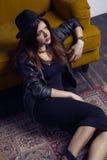 El modelo de Oriente Medio hermoso de la moda con estilo del inconformista está presentando en la alfombra y el sofá amarillo Imágenes de archivo libres de regalías