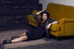 El modelo de Oriente Medio hermoso de la moda con estilo del inconformista está presentando en la alfombra y el sofá amarillo Fotos de archivo libres de regalías