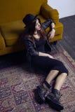 El modelo de Oriente Medio hermoso de la moda con estilo del inconformista está presentando en la alfombra y el sofá amarillo Foto de archivo