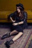 El modelo de Oriente Medio hermoso de la moda con estilo del inconformista está presentando en la alfombra y el sofá amarillo Imagen de archivo