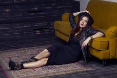El modelo de Oriente Medio hermoso de la moda con estilo del inconformista está presentando en la alfombra y el sofá amarillo Imagenes de archivo