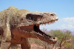 El modelo de un dinosaurio en la arena Imágenes de archivo libres de regalías