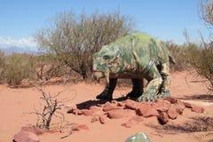 El modelo de un dinosaurio en la arena Imagen de archivo