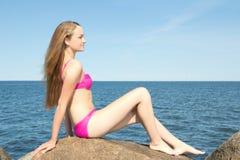 El modelo delgado hermoso en el bikini rosado que se sienta en piedra en rocoso sea Fotografía de archivo