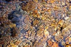El modelo en las piedras despeja el arroyo Imagenes de archivo