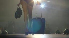 El modelo en vestido corto con la maleta y el bolso camina adelante en el podio en lámparas y humo ligeros almacen de metraje de vídeo